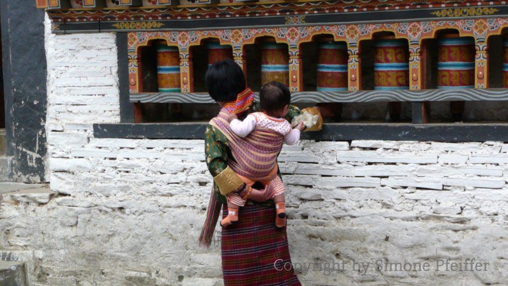 Frau an den Gebetsmühlen im Mongar Dzong.